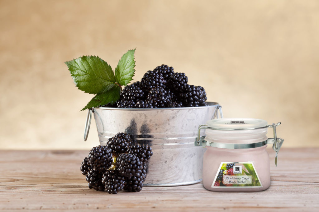 1 Jar of Nabila K's Blackberry Sage Body Butter next to a metal bucket of Blackberries