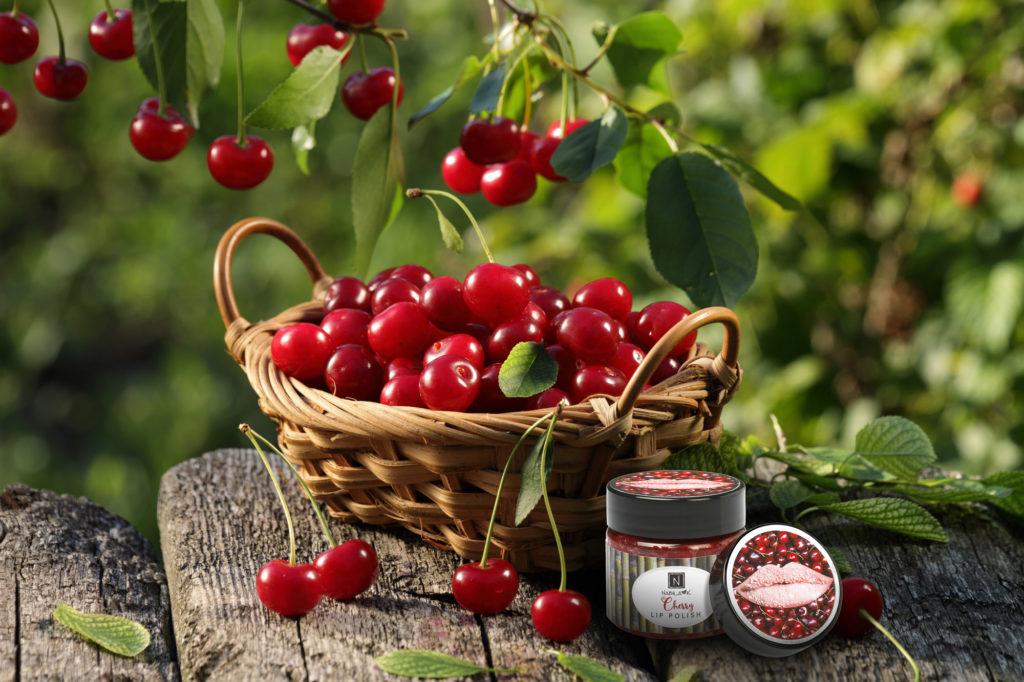 1 Jar of Nabila K's Cherry Lip Polish next to a woven basket full of cherries