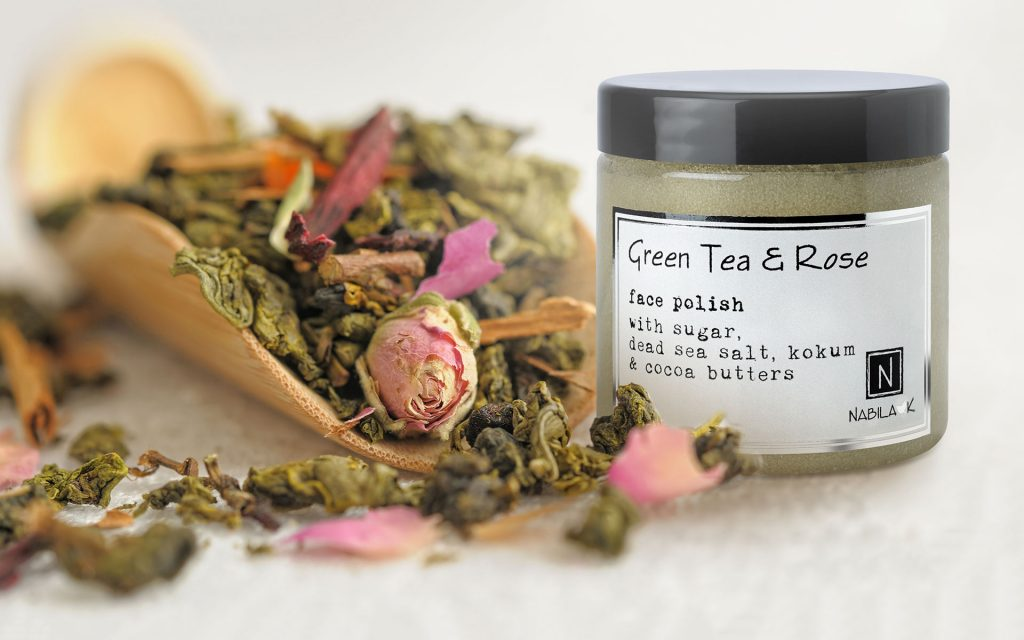 Nabila K's Green Tea and Rose Face Polish with Sugar, dead sea salt, kokum and cocoa butter next to green tea leaves and a rose