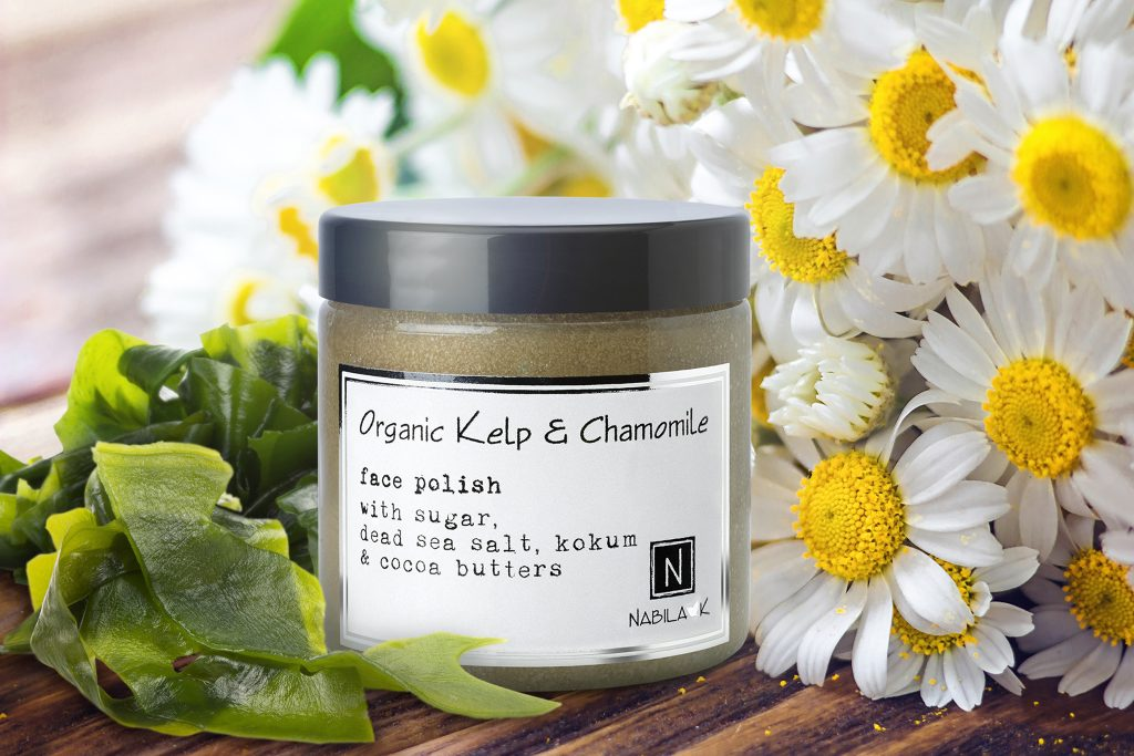 1 Jar of Nabila K's Organic Kelp and Chamomile Face Polish with Sugar Dead Sea Salt, Kokum and Cocoa Butters Next to Flowers