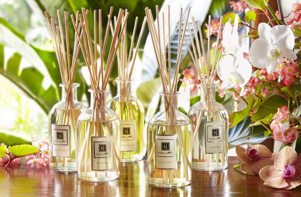 5 of Nabila K's Diffusers with Reeds to Diffuse the Smell next to white and pink flowers