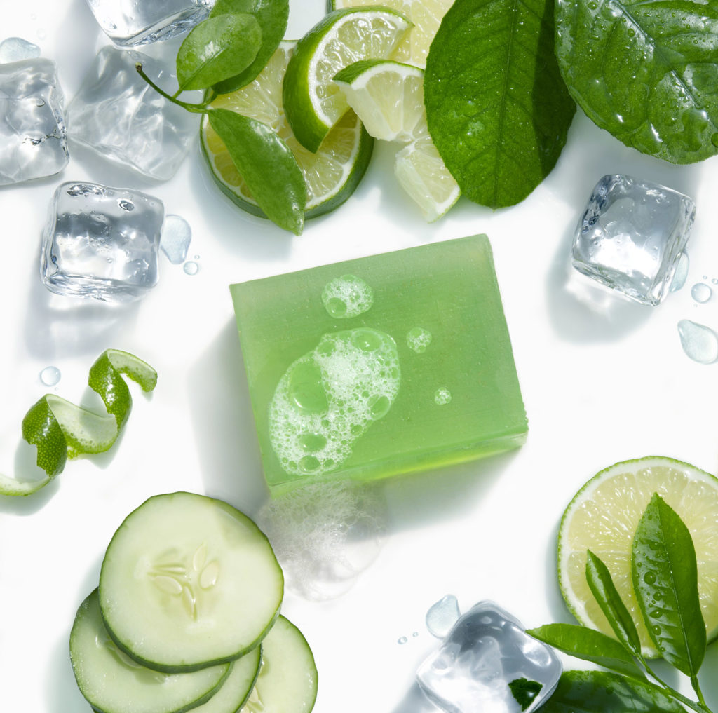 Nabila K's Full Glycerin Soap Placed Aesthetically Between Sliced Cucumbers and Sliced Limes