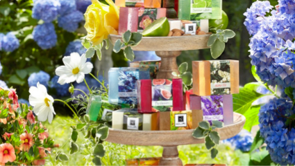 Collection of Nabila K's Glyserine Soap Collection Stacked on a 2 level display piece surrounded by flowers