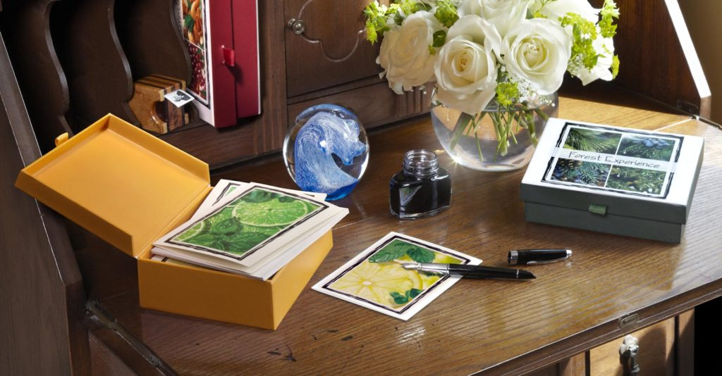 2 Boxes of Nabila K's Cards and Envelopes on a Desk with an uncapped fountain pen, bowl of white flowers, and ink bottle