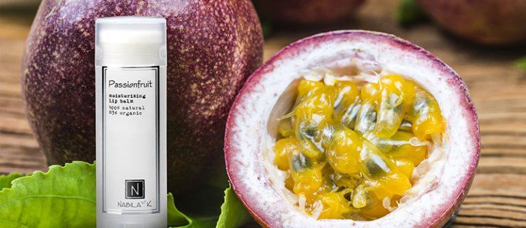 1 of Nabila K's Passion fruit Moisturizing Lip Balm 100% Natural 85% Organic next to a passion fruit cut in half