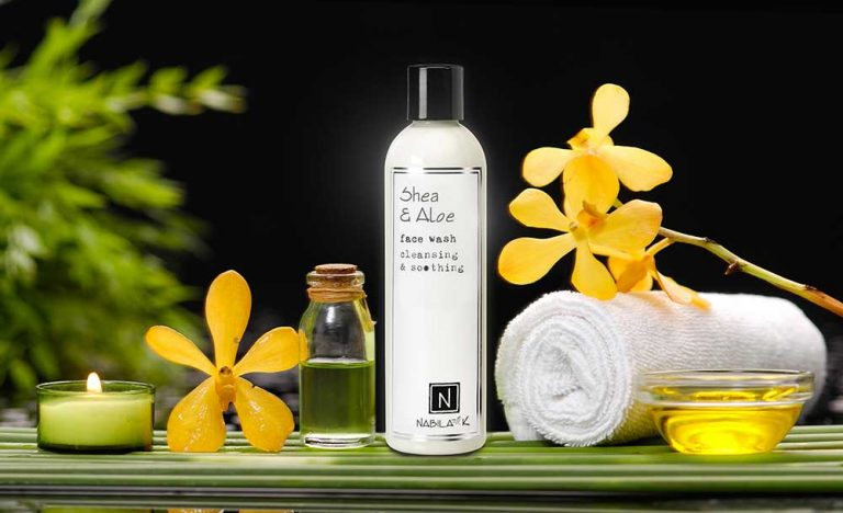 1 Bottle of Nabila K's Shea and Aloe Face Wash Cleansing and Soothing in between a flower, towel, candle and vial of liquid