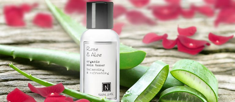 1 bottle of nabila k's rose and aloe organic skin toner next to cut up aloe Vera and rose petals