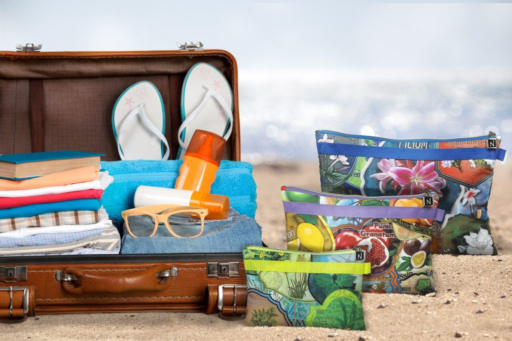 Travel bags on the beach next to the suitcase full of travel accessories.