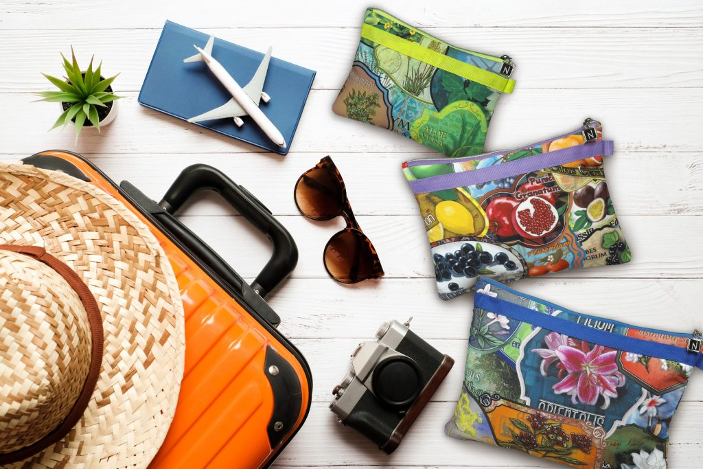 Travel pouches lying on wooden planks with suitcase, sunglasses and camera.